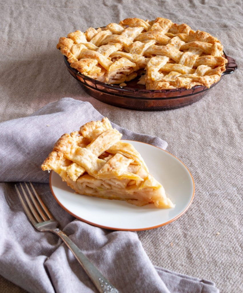 slice of apple pie sitting in front of whole pie