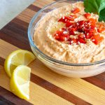 Roasted Red Pepper Hummus garnished with sesame seeds, parsley, and lemon.