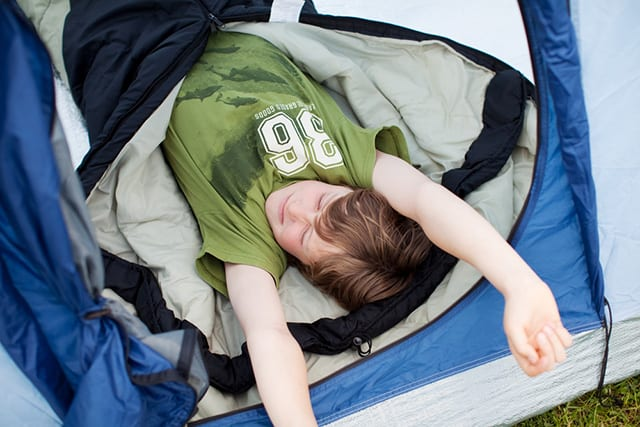 tired boy sleeping in the tent