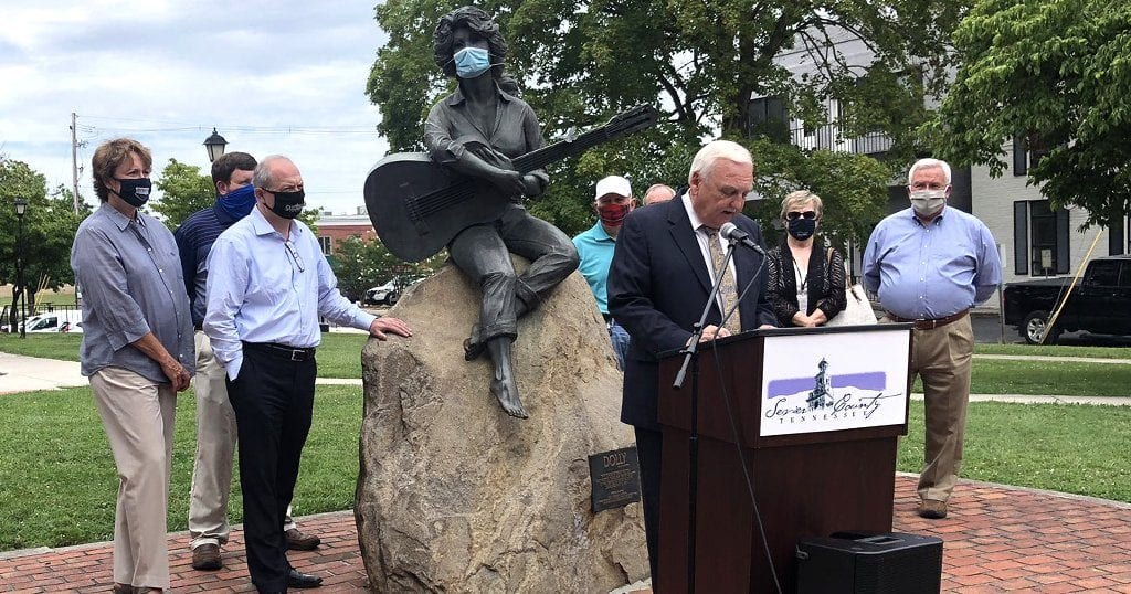 Sevier County Mayor Larry Waters and city officials gather around a masked Dolly Parton statue at the Sevier County Courthouse (photo courtesy of Leslie Ackerson/WBIR)