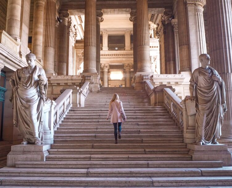 A massive staircase with statues and columns near the entrance of the Palace of Justice in Brussels