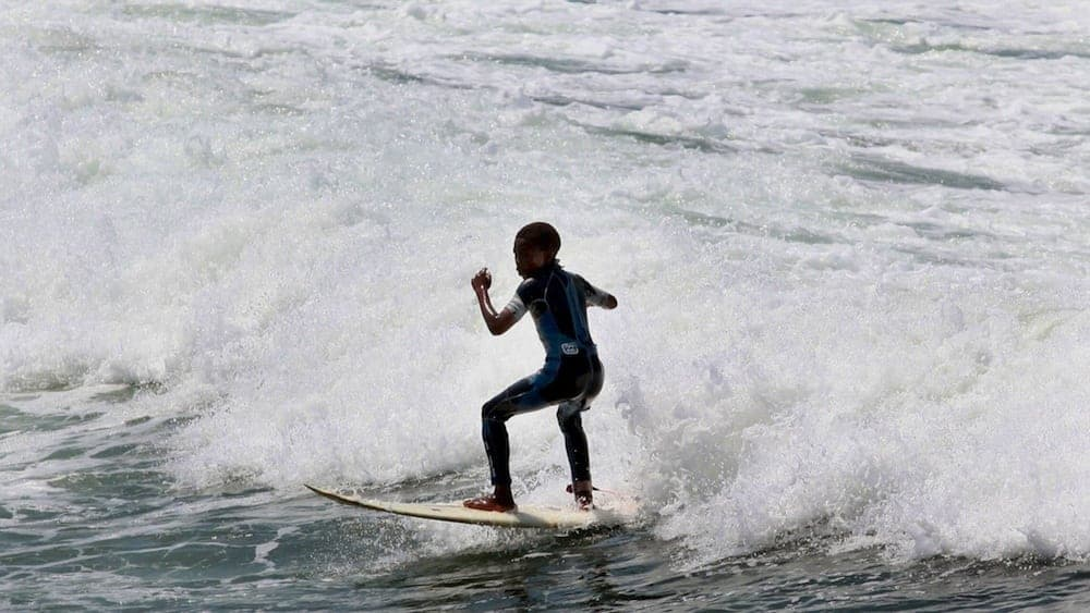 TO GO WITH SAfrica-youth-poverty-surfing-Fbl-WC2010 by Griffin Shea A street child learns to surf at Durban's North Beach on February 13, 2010. Durban is one of nine South African cities hosting the 2010 FIFA Soccer World Cup taking place from June 11 to July 11. AFP PHOTO / RAJESH JANTILAL (Photo credit should read RAJESH JANTILAL/AFP/Getty Images)