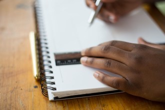Photo illustration of a student writing in a notebook.