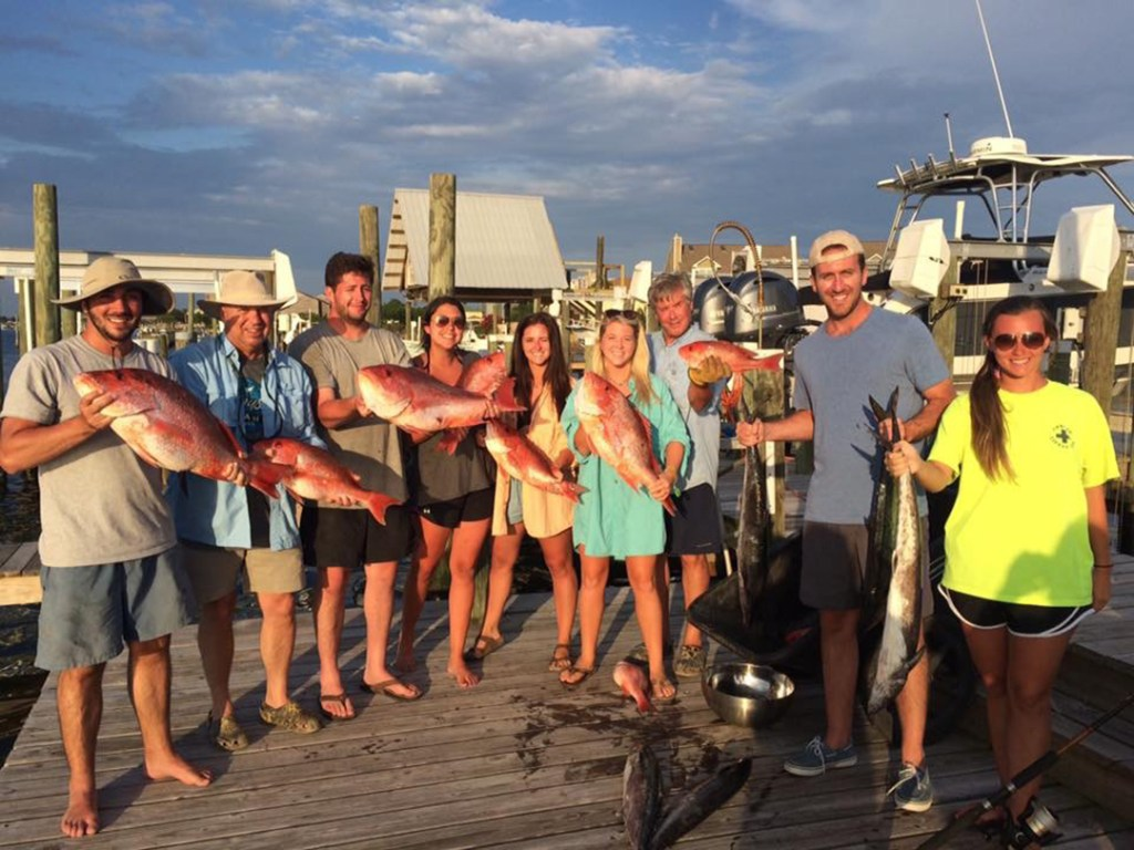 A group holds their catch of the day after deep sea fishing.