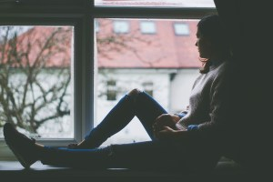 Support for depression - youth counselling - image of a woman looking whistfully out a window
