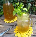 picture of a glass filled with elderflower cordial garnished with mint and lemons