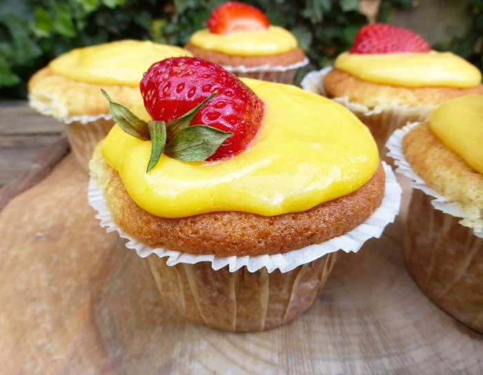 close up of a cupcake topped with lemon curd frosting and a strawberry