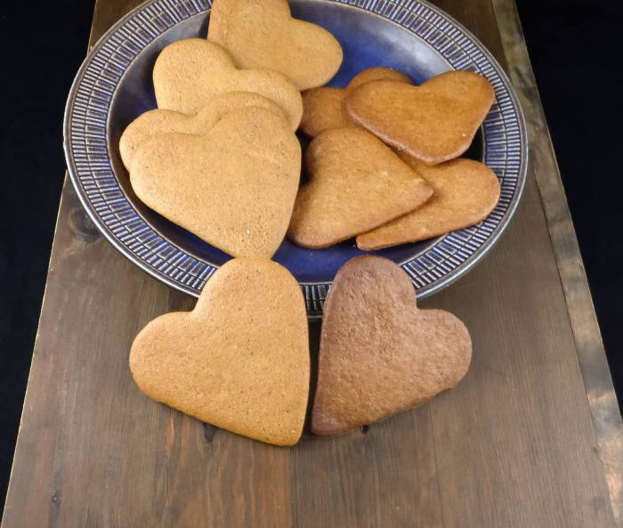 heart-shaped Swedish pepparkakor on a blue plate on top of a wooden board