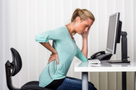 woman with back pain in the office