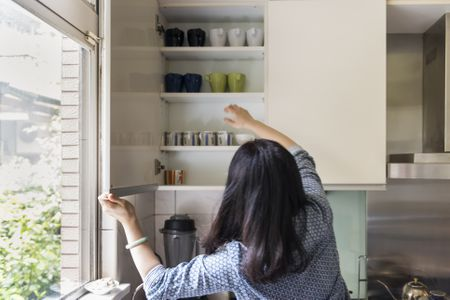 Woman Reaching Into Kitchen Cabinets