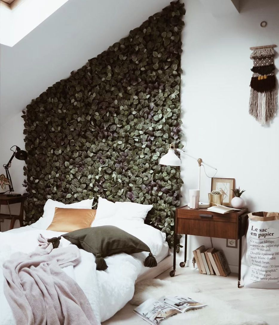 Bedroom with leaves on the wall behind the bed