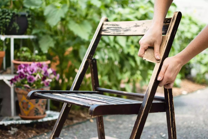 Wooden chair sanded by hand to remove old finish with sandpaper