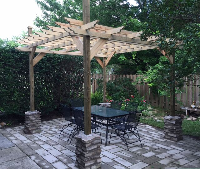 A Pergola With A Table And Chairs Beneath It