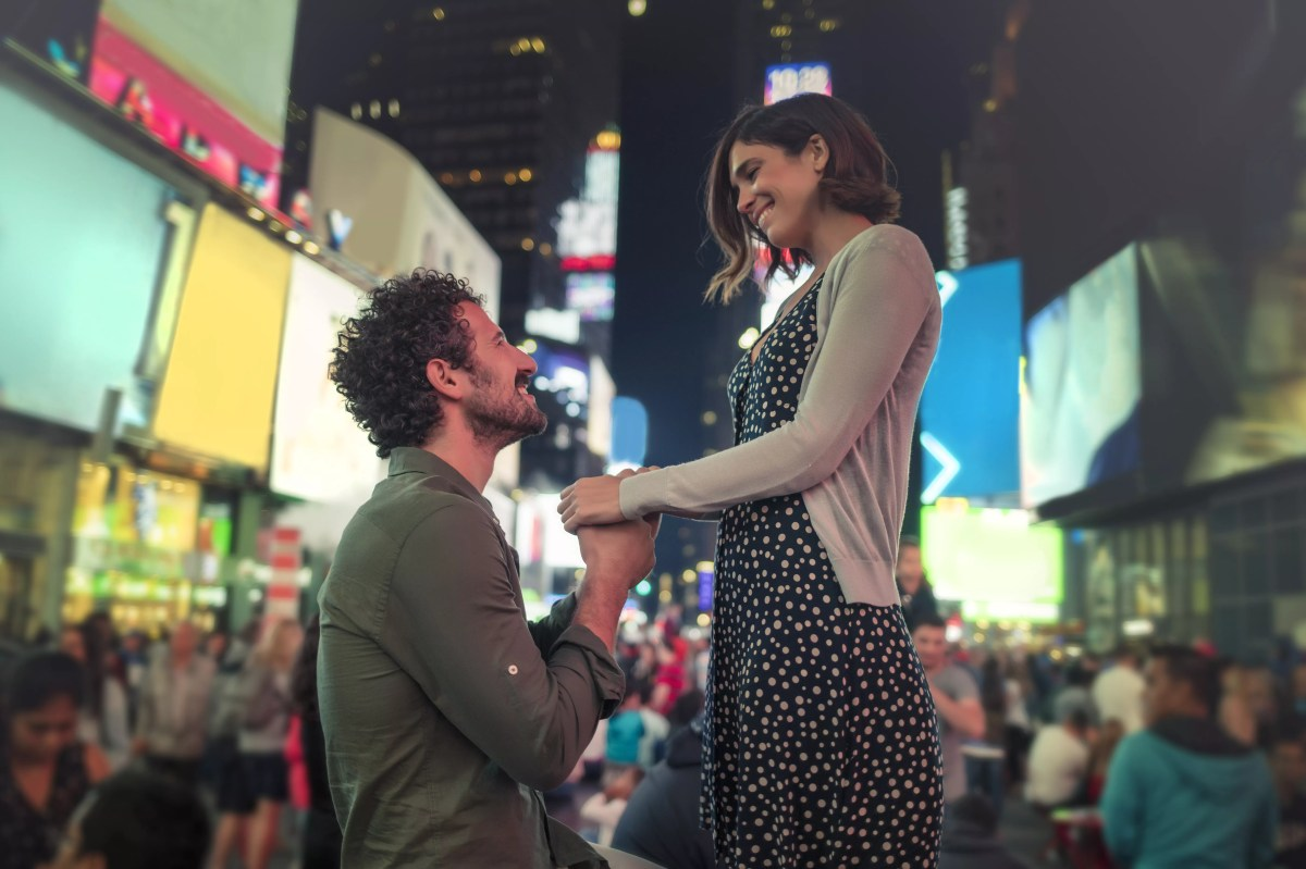 Man on one knee proposing in Times Square, New York, United States, North America