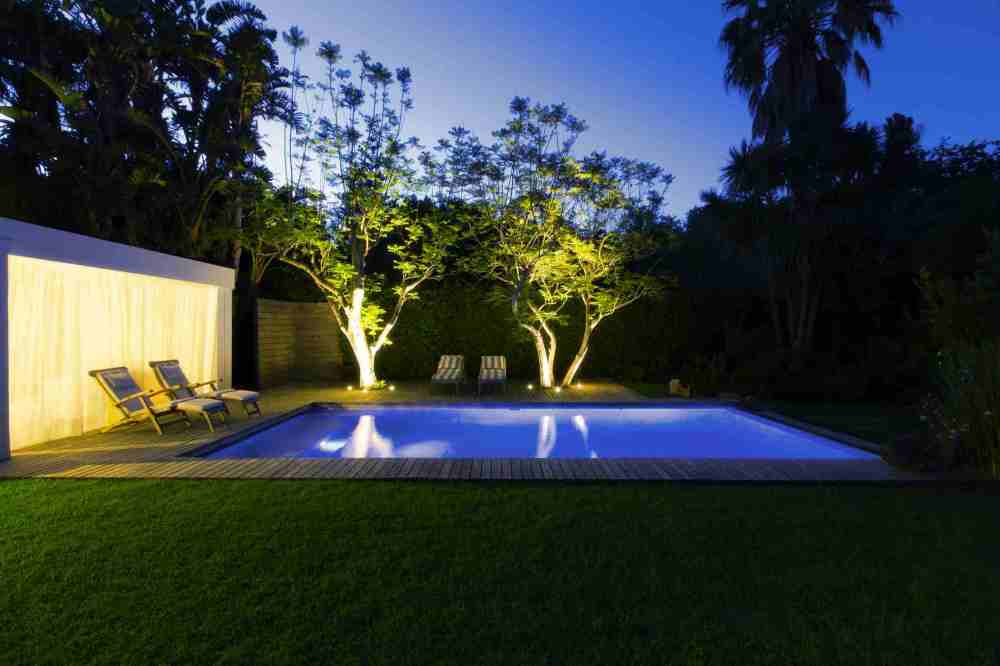 medium resolution of illuminated swimming pool and trees in backyard at dusk