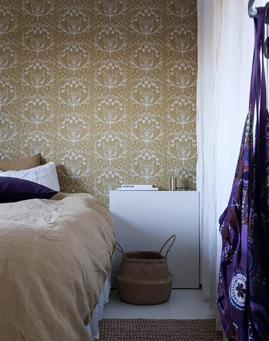 Bedroom with yellow wallpaper behind the bed