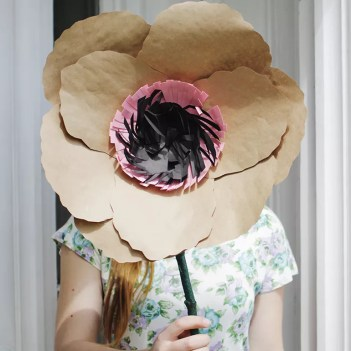 A woman holding a giant paper flower