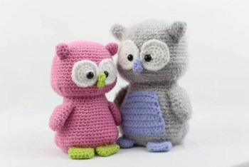 Two colorful crochet owls standing side by side.
