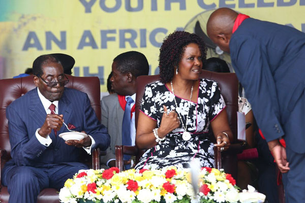 President Robert Mugabe enjoys his cake at Great Zimbabwe monuments yesterday, while his wife, Grace, chats with Zanu PF secretary for youth affairs Pupurai Togarepi. Picture: Aaron Ufumeli