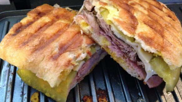 Cubanos are pressed sandwiches with roast pork, ham, pickles, cheese and mustard.