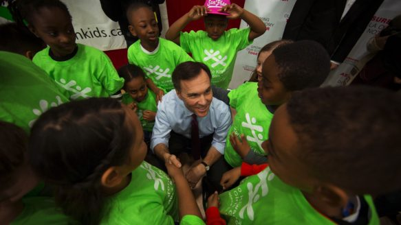 Finance Minister Bill Morneau is surrounded by kids from the Kiwanis Boys & Girls Club after he received his new budget shoes in Toronto on Friday. Tuesday's budget will deliver on a new child benefit to assist parents, big ticket infrastructure spending — and a deficit that is likely to ring in at almost $30 billion in the coming fiscal year.