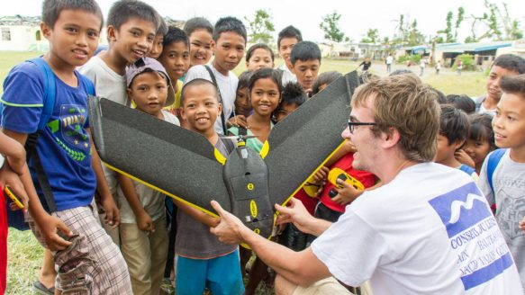 """Alexis Roze, of the non-profit Drone Adventures, shows an eBee mapping """"drone"""" to local kids in the Philippines. The small device was used in the wake of Typhoon Yolanda to help the hard-hit community of Tacloban quickly generate a precise map to be used in disaster relief efforts."""