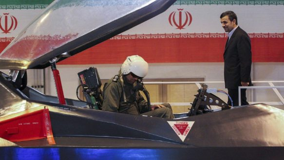 Iranian President Mahmoud Ahmadinejad, centre, listens to an unidentified pilot during a ceremony to unveil Iran's newest fighter jet, Qaher-313, or Dominant-313,which officials claim can evade radar, in Tehran, Iran, Saturday.