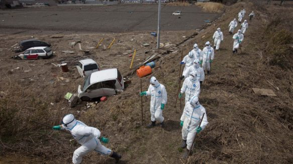 In this April 7, 2011 file photo, Japanese police, wearing suits to protect them from radiation, search for victims inside the deserted evacuation zone around the Fukushima Dai-ichi nuclear reactors.