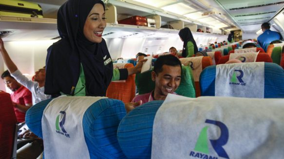 A Rayani Air flight crew member, left, shares a light moment with passengers aboard one of the company's Boeing 737s, while on the ground Tuesday at Kuala Lumpur International Airport.