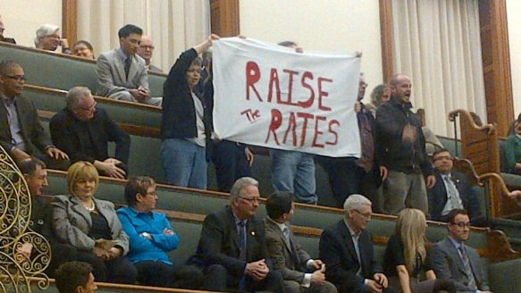 "Anti-poverty protesters unfurl a banner and chant ""Raise the rates!"" from the public gallery at Queen's Park last year. (April 24, 2012)"