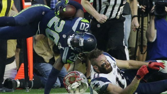 Seattle Seahawks cornerback Jeremy Lane (20) is tackled by New England Patriots wide receiver Julian Edelman (11) after intercepting New England Patriots quarterback Tom Brady during the first half of NFL Super Bowl XLIX football game Sunday, Feb. 1, 2015, in Glendale, Ariz. Edelman was later hit in the game and looked like he was suffering from a concussion.