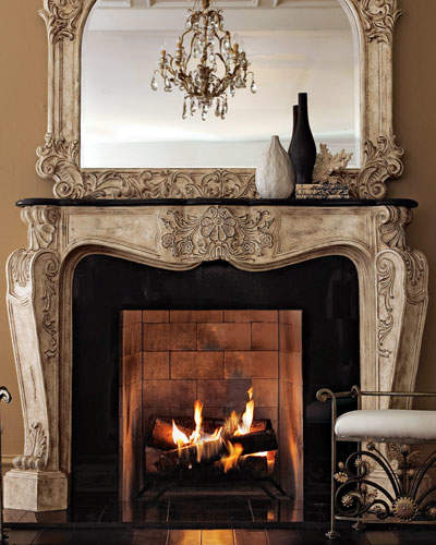 Cast-stone mantel topped by black stone. Mantel has an antique-parchment finish with golden highlights on a shell and foliage motif.