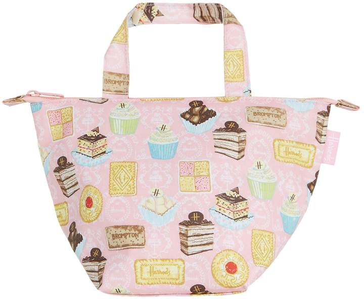 Harrods makes it easier with its - charming memento from their world-famous store, Afternoon Tea lunch bag printed with scrumptious cakes and biscuits alongside the iconic Harrods logo and Crafted in practical, wipe-clean PVC-coated cotton, it is finished with a secure zip fastening and a padded, insulated interior to keep your lunch cool.