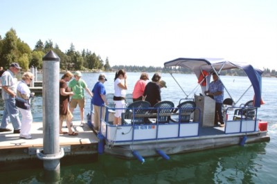 LEAVING FOR ISLAND - Some of the nearly 60 members of Lakewood Historical Society and their guests board a pontoon boat at American Lake Park for a ride out to Silcox Island. The group toured the island, learned aspects of its history including such items as electricity was brought from the shore in 1968. Prior to that time, residents used lanterns and fireplaces.