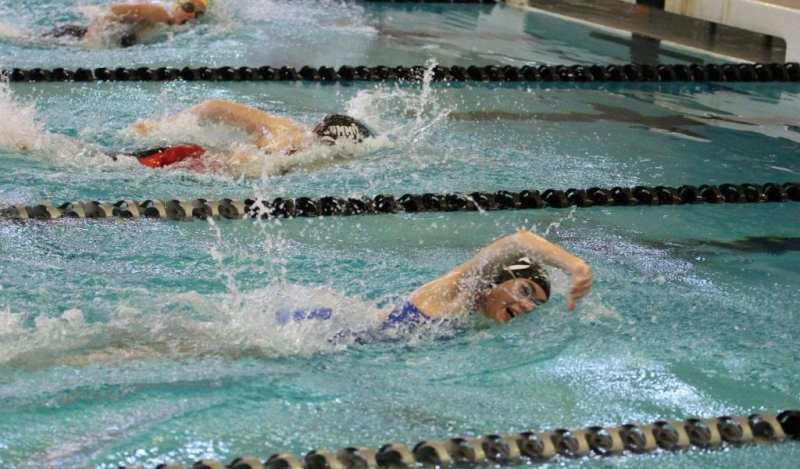 Summit Swim team members race down the pool during a meet.