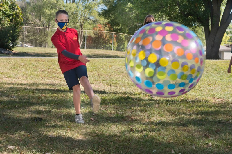 A Camp Raven camper kicks a large, colorful ball across the field.