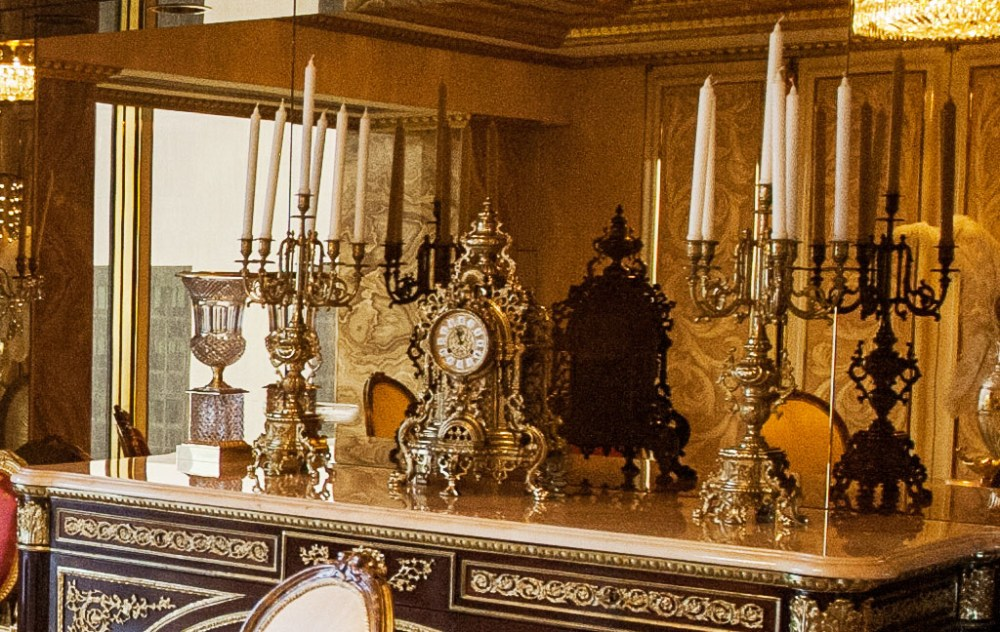 A stunning antique clock sits on the marble-topped mantle, framed by two elegant candelabras