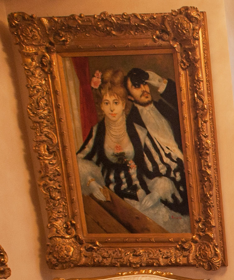 On the wall sits a a reproduction of Renoir's La Loge - the original is in the Courtald gallery in London