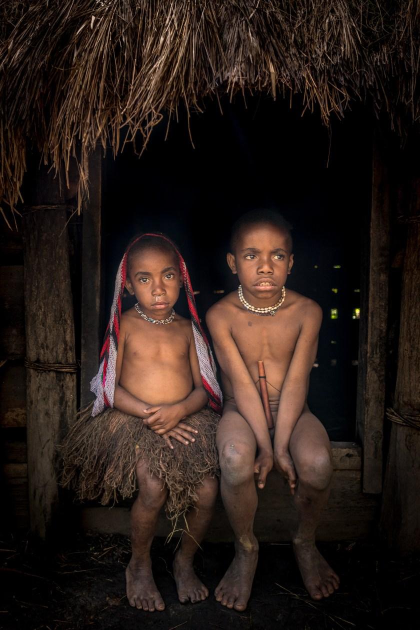 Seorang anak laki-laki dan perempuan dari suku Dani duduk di dalam sebuah pondok di desa mereka ... sebagian besar anggota suku tidak berbahasa Indonesia atau Inggris