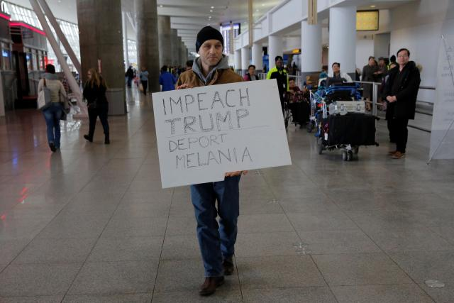 A protester walks through Terminal 4 at John F. Kennedy International Airport