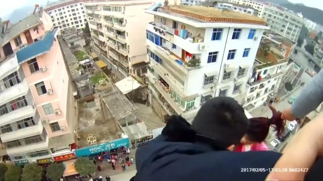 Police arrived to find a man holding his wife by her pony tail as she tried to jump to her death from the roof of a building
