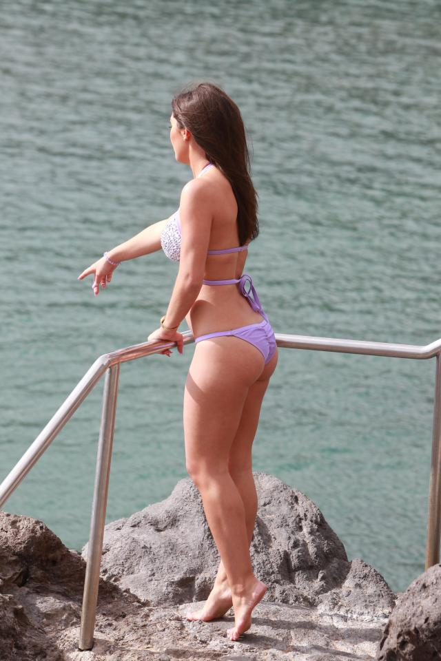The bikini babe pointed down to her man from the railing above the sea
