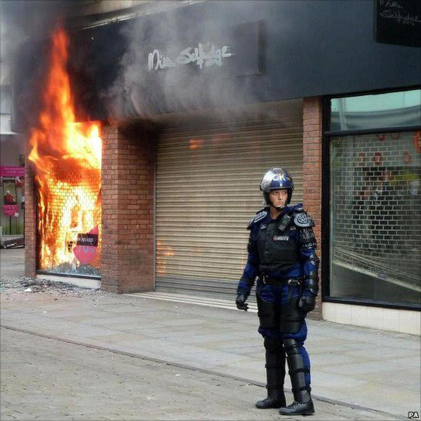 Red, riot and blue . . . PC Reeve at a burning Manchester store during 2011 riots