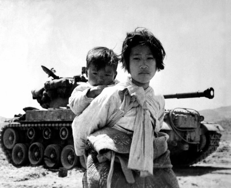 With her brother on her back a war weary Korean girl tiredly trudges by a stalled tank, at Haengju, Korea. June 9, 1951