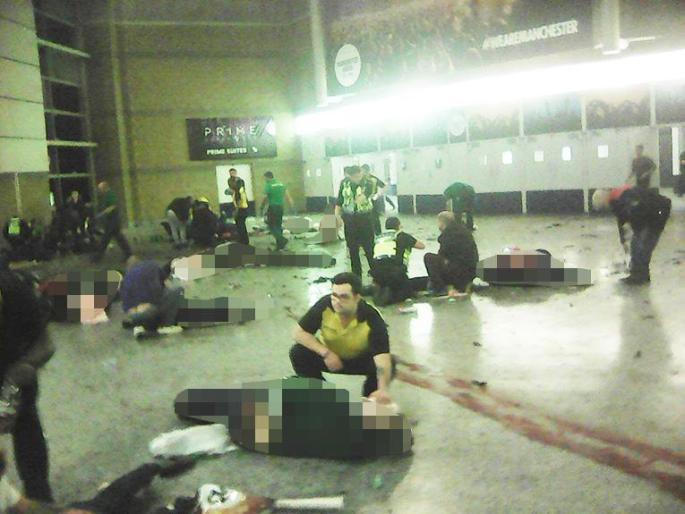 Helpers attend to people inside the Manchester Arena after a suicide bomber detonated an explosive device