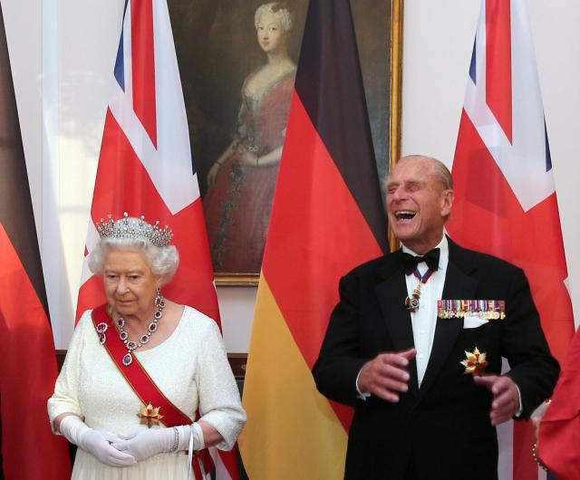 Prince Philip chuckles as he waits to greet guests at a state banquet in Berlin in 2015 alongside The Queen