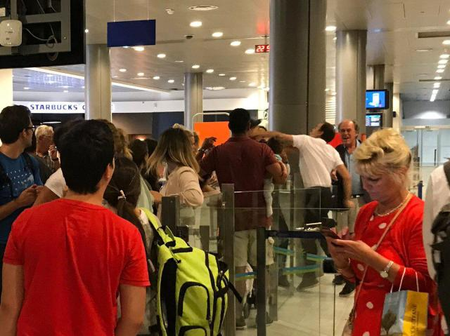 The airport worker punched an easyJet passenger who was holding his baby following a grueling 13-hour delay, witnesses said
