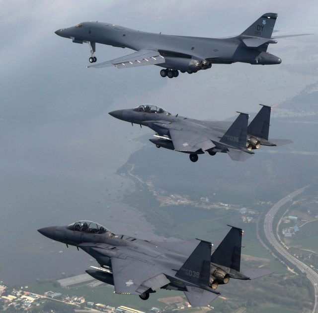 A US Air Force B-1B bomber, top, flies with South Korean fighter jets