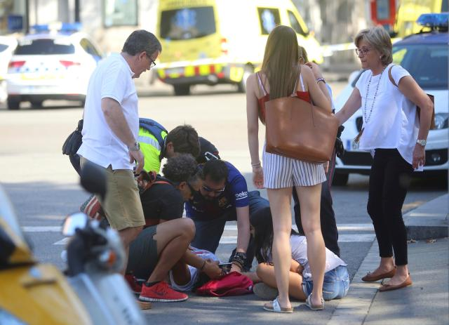 Witnesses work to tend to the injured in the aftermath of the van horror
