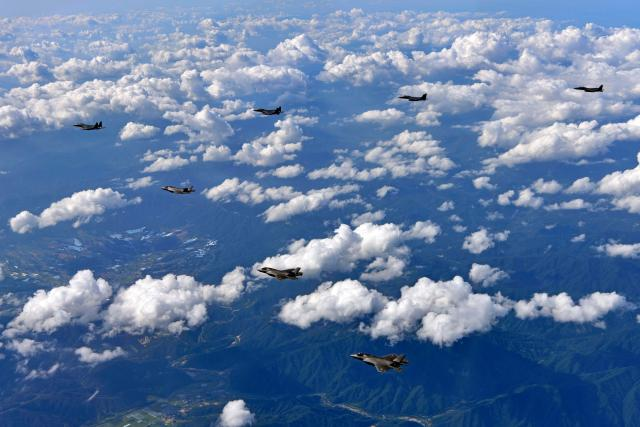 US Marine Corps F-35B fighter jets (front) and South Korean air Force's F-15K fly over South Korea